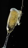 Glass of champagne with splash, isolated on black background Stock Photo