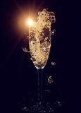 Glass of champagne with splashes Stock Photos