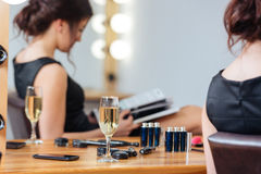 Glass of champagne standing on table near woman reading magazine. Closeup of glass of champagne standing on the table near young woman reading magazine in Stock Images
