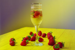 Glass of champagne with strawberries. On the bright yellow wooden table Royalty Free Stock Photo