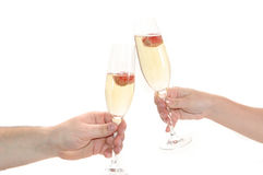 Glass of champagne with strawberry. Glasses of champagne with strawberry in hands on black background Stock Image