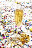 Glass of champagne with streamers and confetti Royalty Free Stock Photos