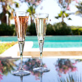 Glass of champagne. On the glass table in outdoor resort bar Stock Photos