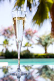 Glass of champagne. On the glass table in outdoor resort bar Royalty Free Stock Photography