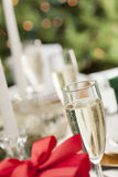Glass of Champagne on Table Place Setting and Christmas Gift Royalty Free Stock Images