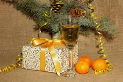 A glass of champagne, tangerines and present for the new year Stock Images