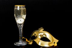 Glass of champagne, watch and venetian mask Stock Photo