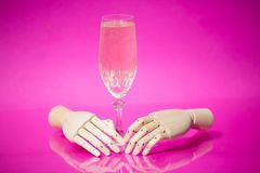 Glass of champagne with wooden hands on pink background Royalty Free Stock Image
