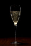 Glass with champagne on a wooden table Stock Photos
