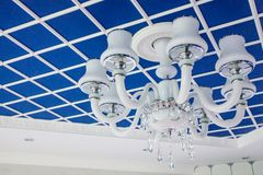 Glass chandelier on the ceiling. Stylish blue ceiling, divided into squares. Royalty Free Stock Photos