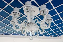 Glass chandelier on the ceiling. Stylish blue ceiling, divided into squares. Royalty Free Stock Photo