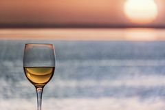 Glass of Chardonnay White Wine Overlooking the sea. During the sunset stock image