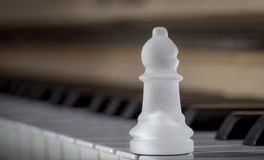 Glass chess bishop on the piano (matte) Royalty Free Stock Photography