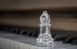 Glass chess bishop on the piano (shiny) Royalty Free Stock Images