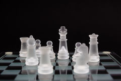 Glass Chess on a black background. Minimum business concept. The king is surrounded by other figures. Glass Chess on a black background. Minimum business Stock Photos