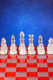 Glass chess on the chessboard. Blue background Stock Images