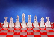 Glass chess on the chessboard. Blue background Royalty Free Stock Photography