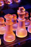 Glass chess on a chessboard lit by blue and orange light Royalty Free Stock Image