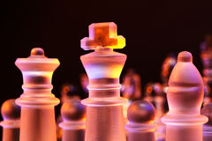 Glass chess on a chessboard lit by blue and orange light Royalty Free Stock Images