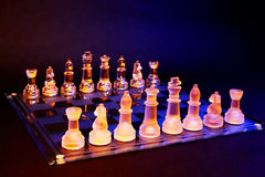 Glass chess on a chessboard lit by blue and orange light Stock Photo