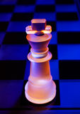 Glass chess on a chessboard lit by blue and orange light Royalty Free Stock Photo