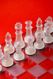 Glass chess on the chessboard. Red background Royalty Free Stock Image