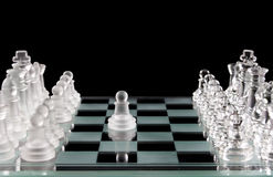Glass chess and the first move Royalty Free Stock Images