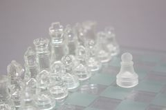 Glass chess on a gray background. Royalty Free Stock Photography