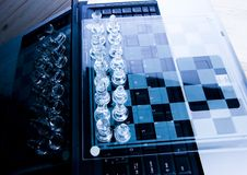 Glass chess & Laptop. Chess - a game for two people that is played on a board with 64 black and white squares called a chessboard Stock Images