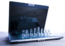 Glass chess & Laptop. Chess - a game for two people that is played on a board with 64 black and white squares called a chessboard Stock Image