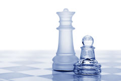Glass chess. A pawn and a queen. Blue toned. It is isolated on a white background Royalty Free Stock Photography