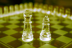 Glass chess pieces. A set of glass chess pieces with the king and bishop in the center of the board Stock Photos