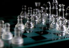 Glass Chess Pieces Are Defending The King On Board In Dark Stock Photos
