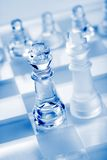 Glass chess pieces with blue light Stock Photography