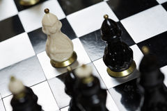 Glass chess pieces on a chessboard Stock Photo