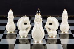Glass chess pieces on a chessboard Royalty Free Stock Photos
