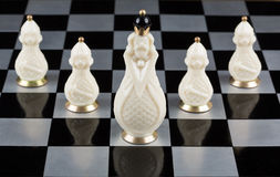 Glass chess pieces on a chessboard Royalty Free Stock Image