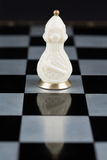 Glass chess pieces on a chessboard Stock Photography