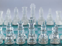 Glass Chess Pieces on a Frosted Glass Royalty Free Stock Photography