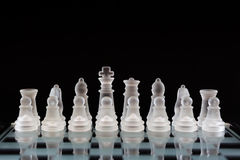 Glass chess pieces in the initial order before the game on a black background. Business concept. Glass chess pieces in the initial order before the game on a Royalty Free Stock Photography