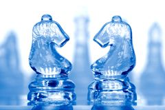 Glass Chess Pieces With Blue Light Stock Photos