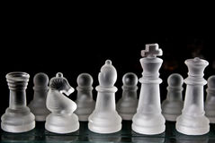 Glass chess set. A frosted glass chess set on a glass chess board with a dark background with plenty of room for copy or text Royalty Free Stock Photography