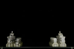 Glass Chess Set. A glass chess set illuminated softly with studio lights with the background intentionally darkened Stock Images