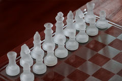 Glass Chessboard. With white chess pieces made of frosted glass, standing on red wood Royalty Free Stock Photography