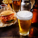 Glass of chilled beer with a hamburger Stock Photos