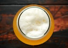 Glass of chilled unfiltered beer with on wooden table.  royalty free stock images