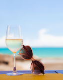 Glass of chilled white wine and sunglasses on table near the beach Stock Photography