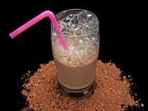 Glass of Chocolate Milk. Glass of cold chocolate milk sitting atop a small amount of cocoa powder.  Black background Stock Image