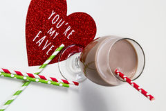 Glass of chocolate milk with red and green paper straws and red glitter heart Stock Photo