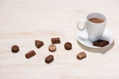 Glass of chocolate milk and variety chocolates  on table Stock Photos